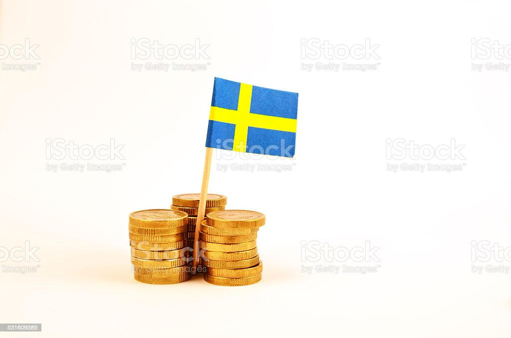 Coin piles and a swedish flag stock photo