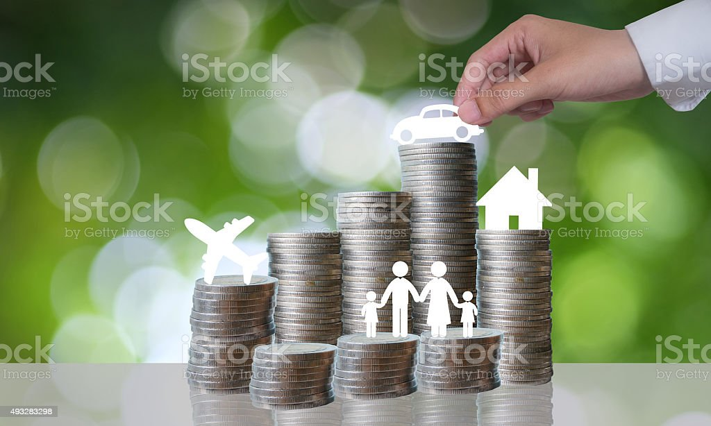 Coin stacks with travel family home car on business man hand on green...