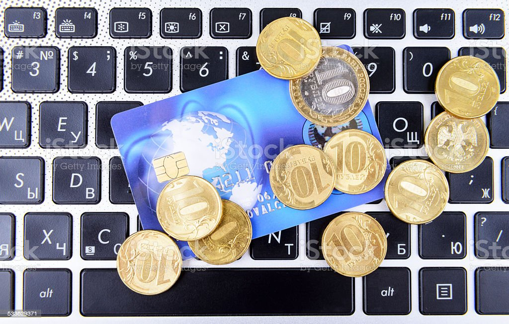 coins and a bank card on the keyboard stock photo