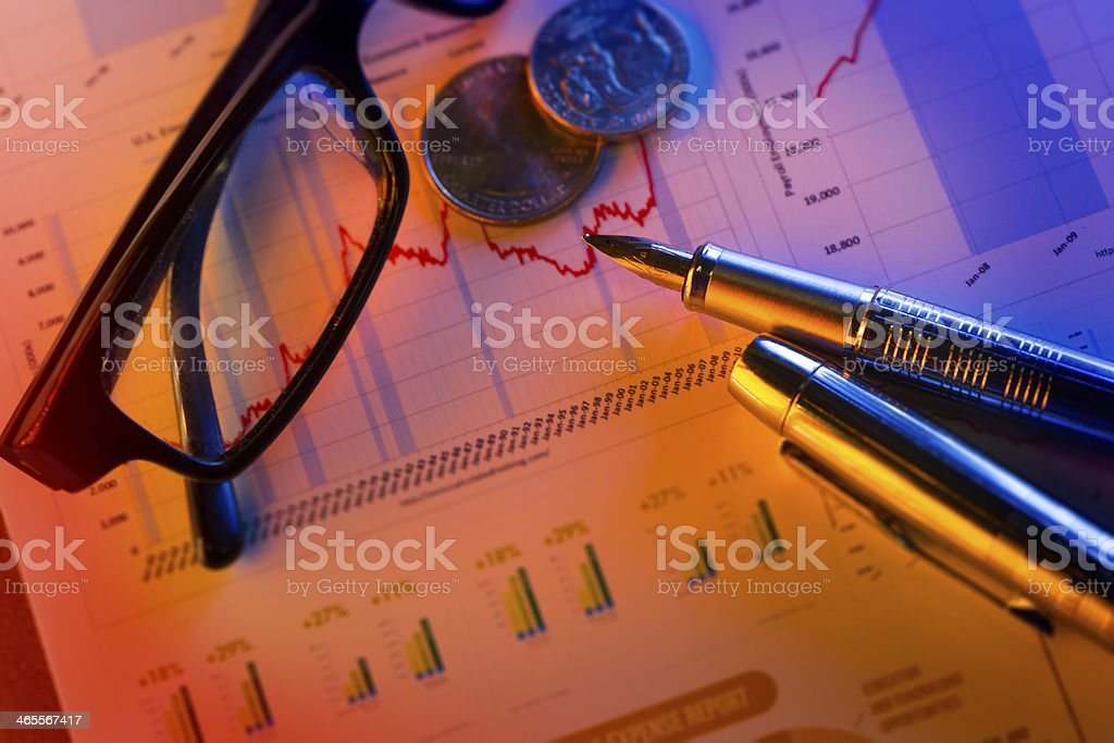 coins and fountain pen on the stock page royalty-free stock photo