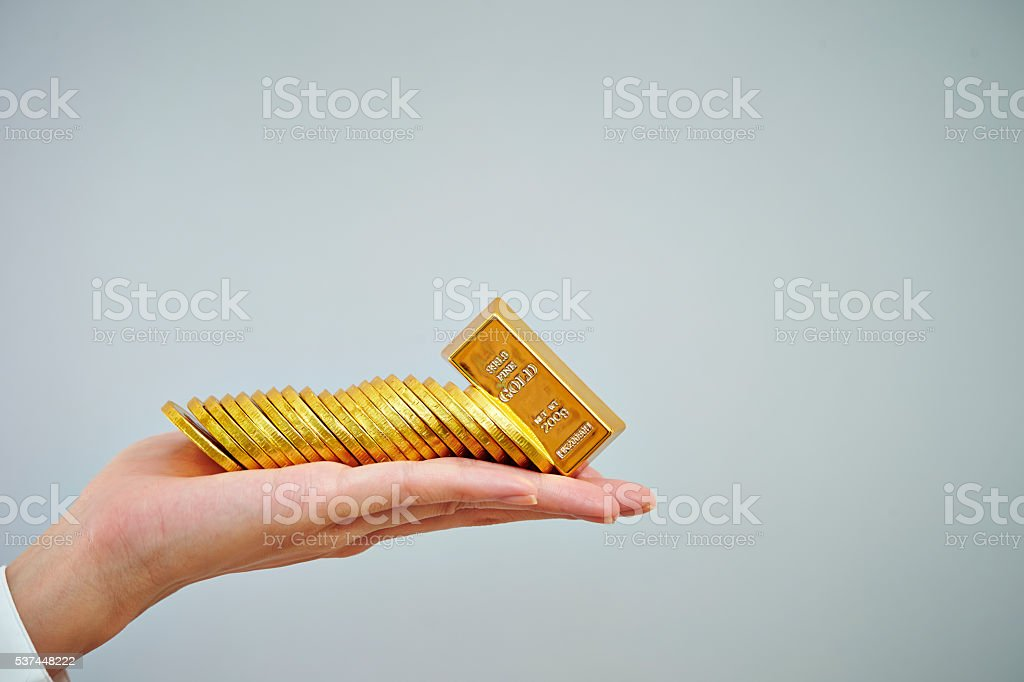 Coins and gold bar on hand stock photo