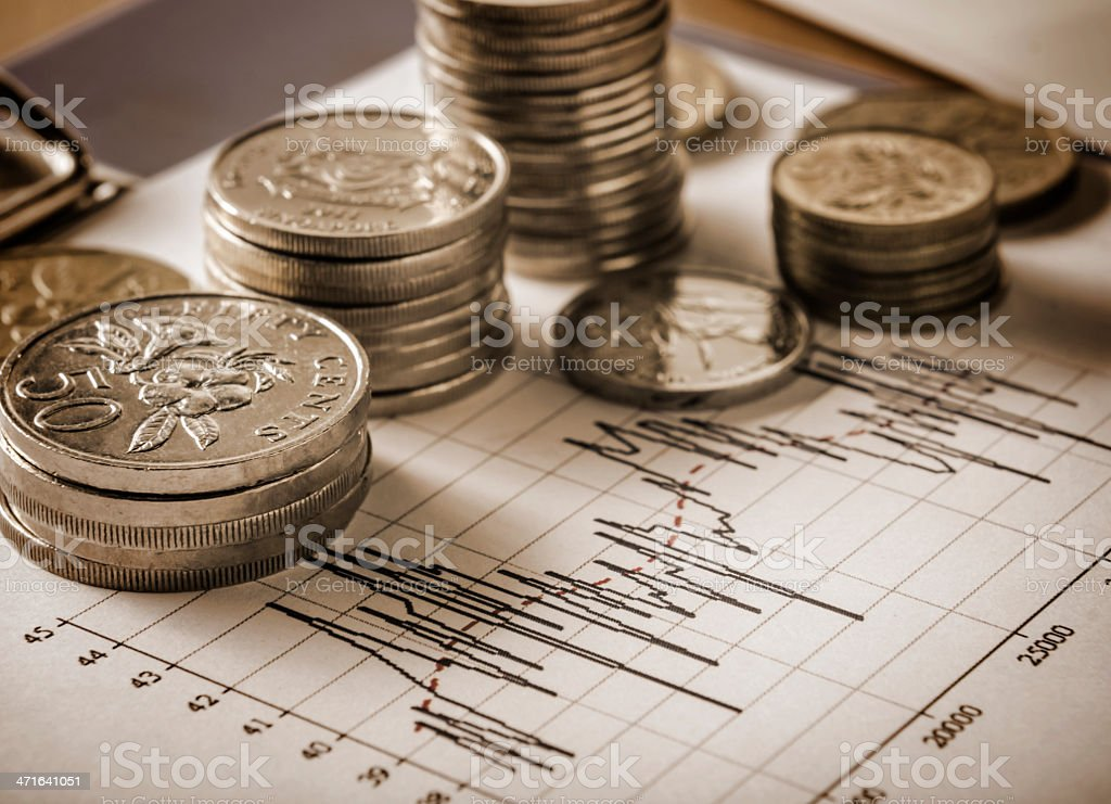 Coins and graph in sepia tone stock photo