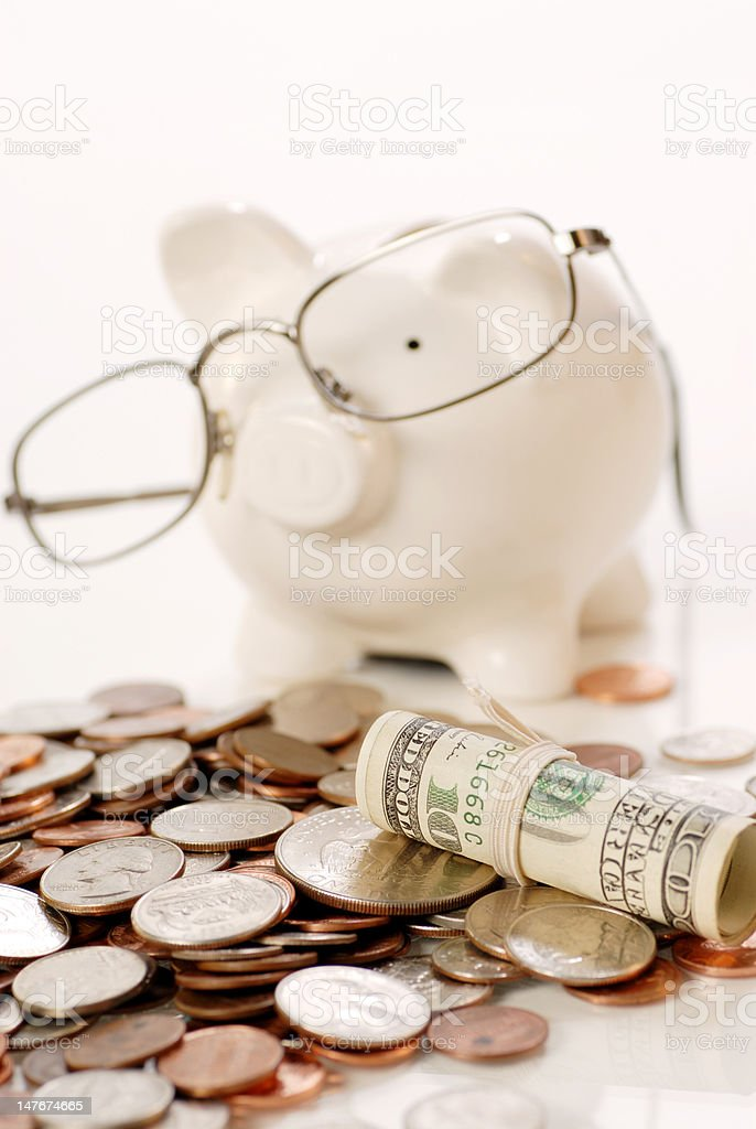 coins and piggy bank with glass. stock photo