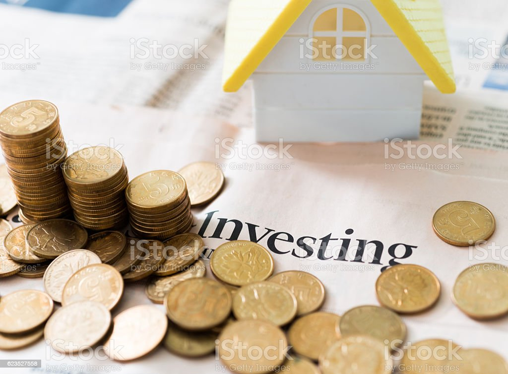 Coins and small house on financial newspapers stock photo