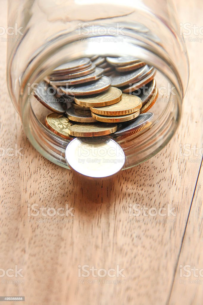Coins are in the glass Jar on wooden background stock photo