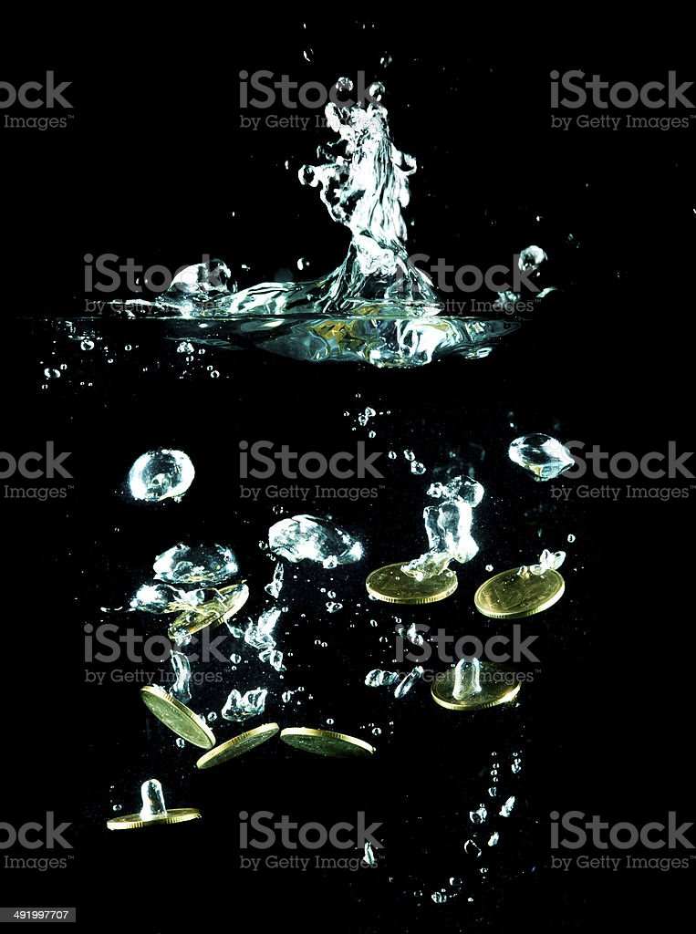 coins falling down to water stock photo