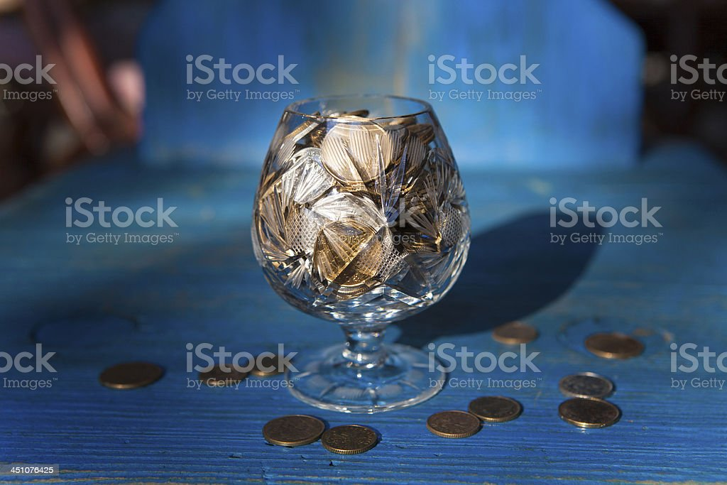 Coins in a crystal cognac glass royalty-free stock photo
