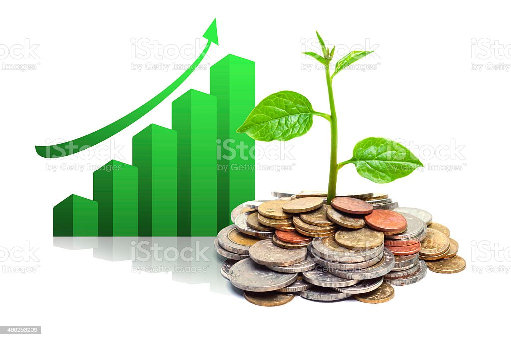 Coins in a pile with a plant growing out of them with graph  stock photo