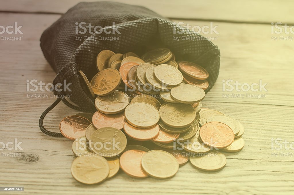 Coins in Black Bag in Bright Light , Vintage Style stock photo