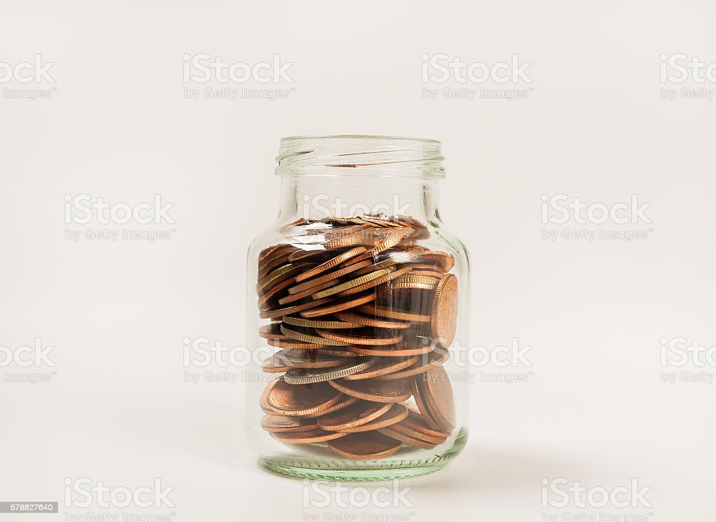 Coins in glass bottle on white background stock photo