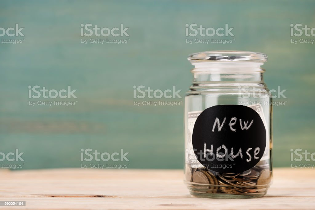 coins in glass can with sign new house on wooden table, piggy bank savings stock photo