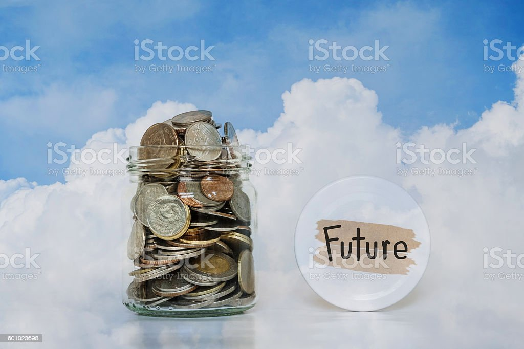 Coins in glass jar ,saving money for Future, on sky stock photo