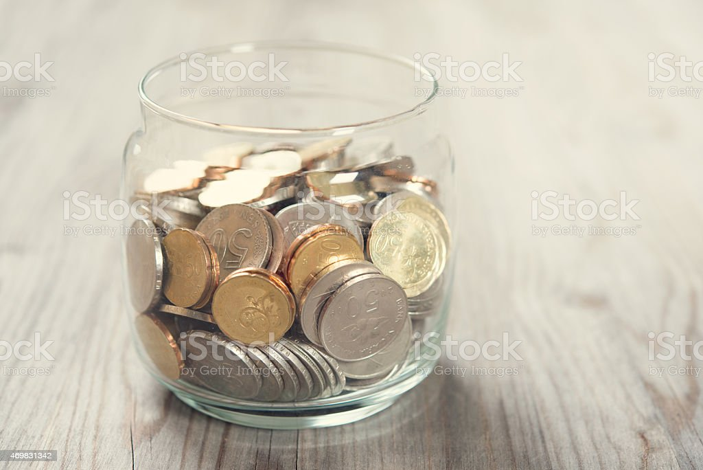 Coins in glass money jar stock photo