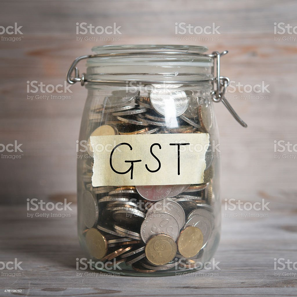 Coins in money jar with gst labe stock photo