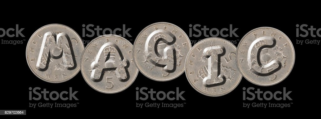 MAGIC – Coins on black background stock photo