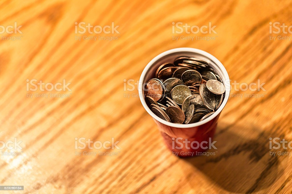 US Coins Piled in Plastic Money Cup stock photo