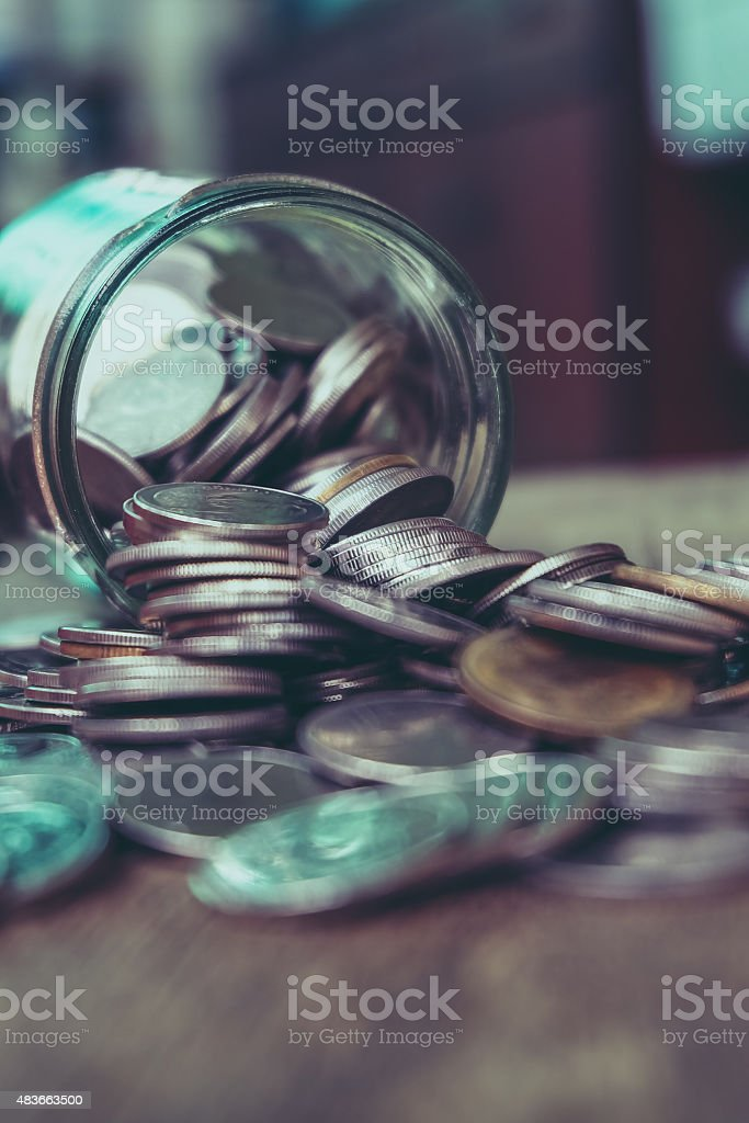 Coins spilling out of a glass bottle stock photo
