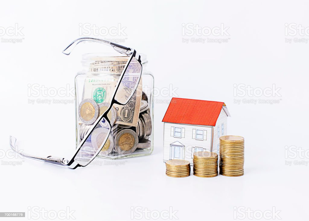 coins stack with paper house and eye glasses with saving bottle stock photo