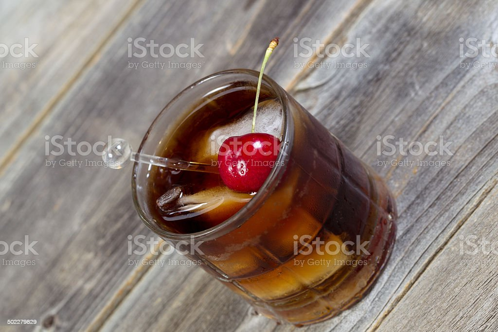 Cola and Rum with ripe cherry and ice in Glass stock photo