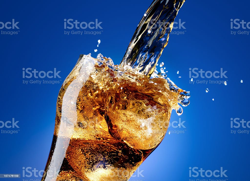 Cola with a large splash, isolated on blue stock photo