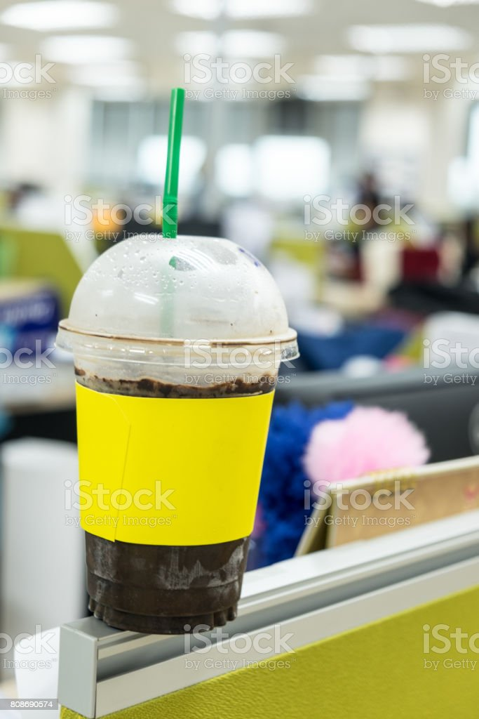 Cola with ice and straw in take away cup with office background stock photo