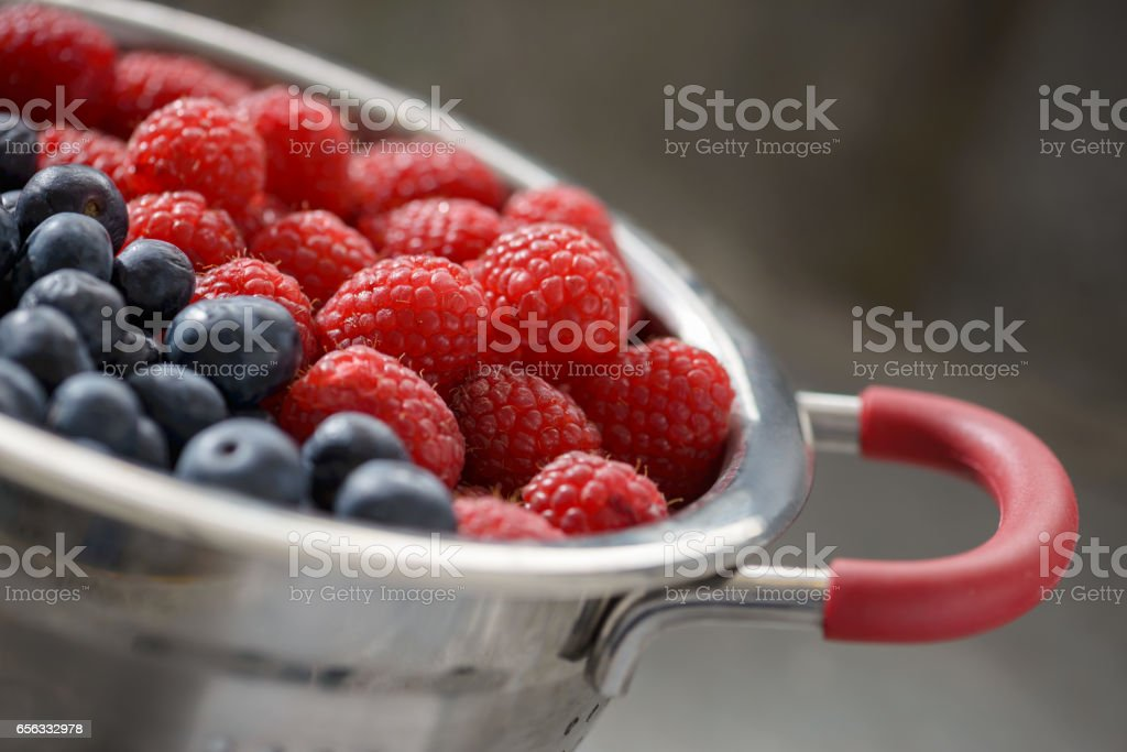 Colander of blueberries and raspberries stock photo