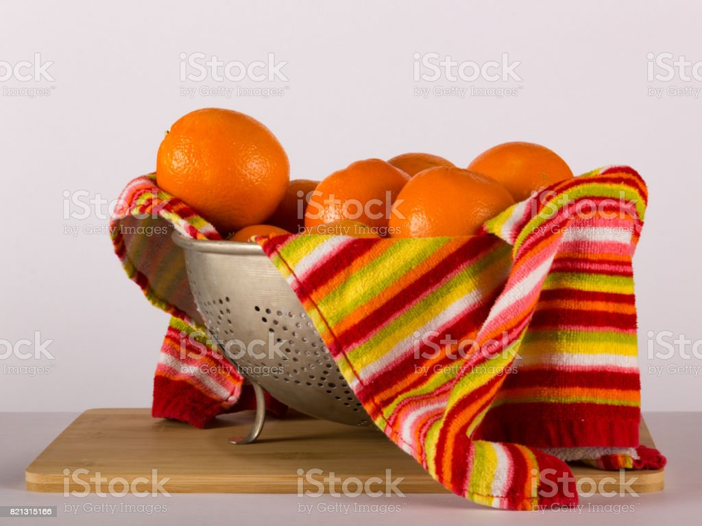 Colander of Citrus and Apple Fruit with Towel stock photo