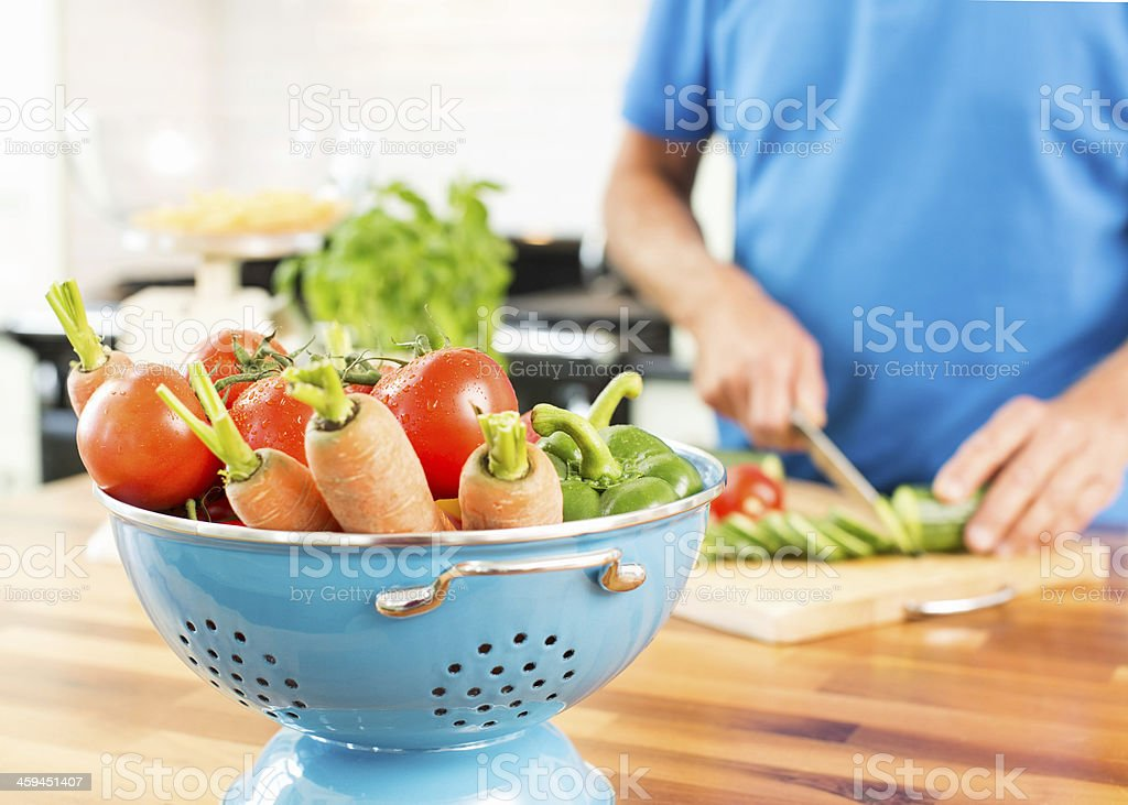 Colander Of Fresh Vegetables On Counter In Kitchen. stock photo