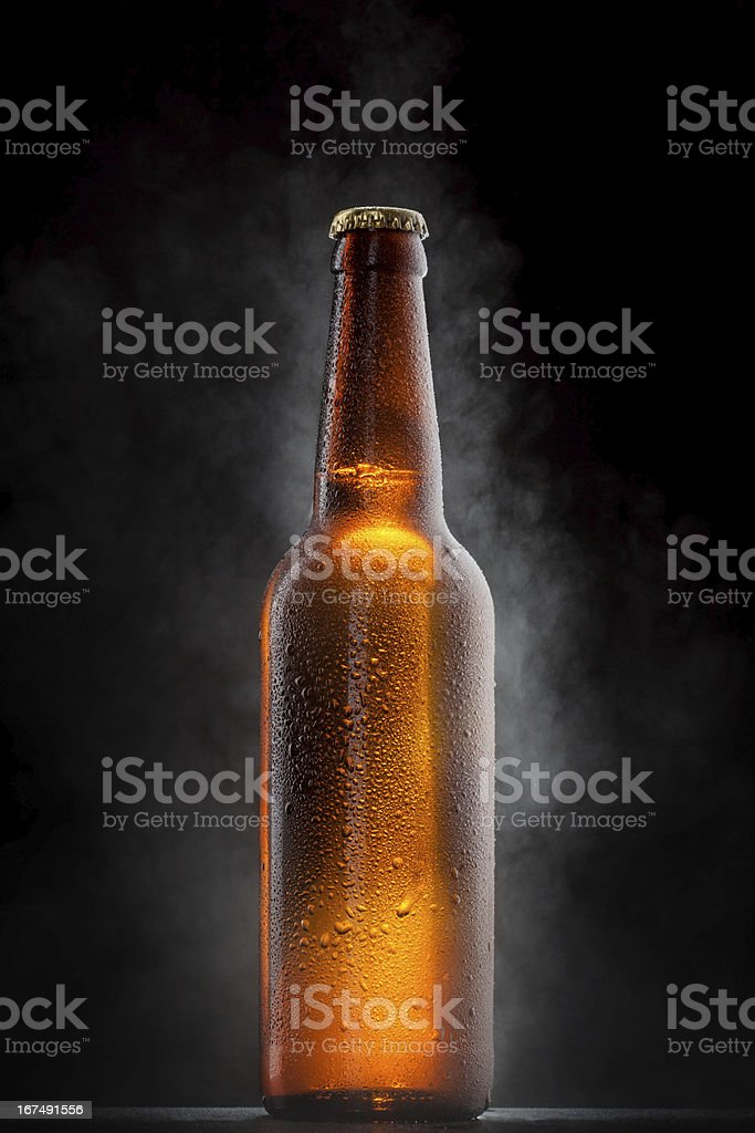 Cold beer bottle with drops, frost and vapour on black stock photo