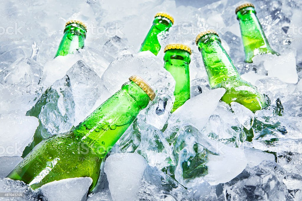 Cold beer bottles on ice stock photo