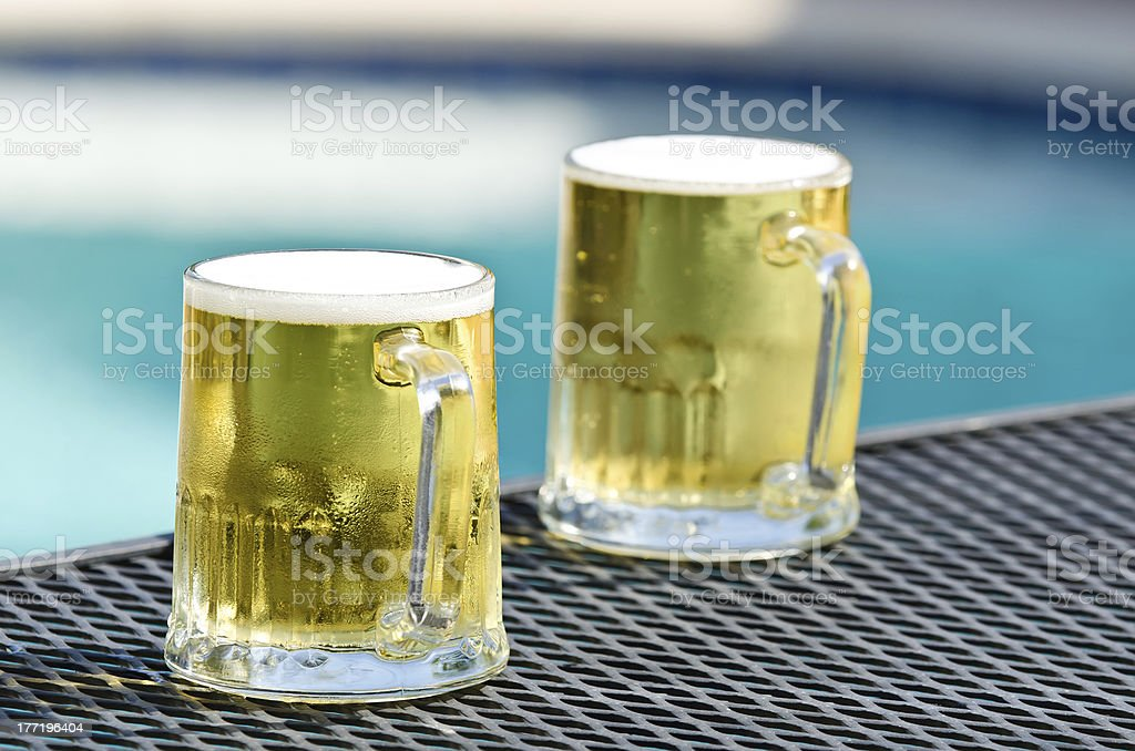 Cold beer glasses by pool royalty-free stock photo
