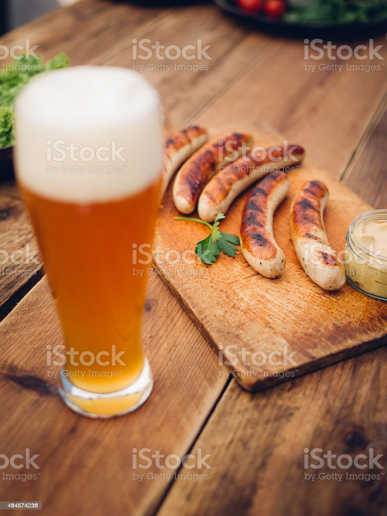 Cold beer with grilled bratwurst sausages on a wooden table stock photo
