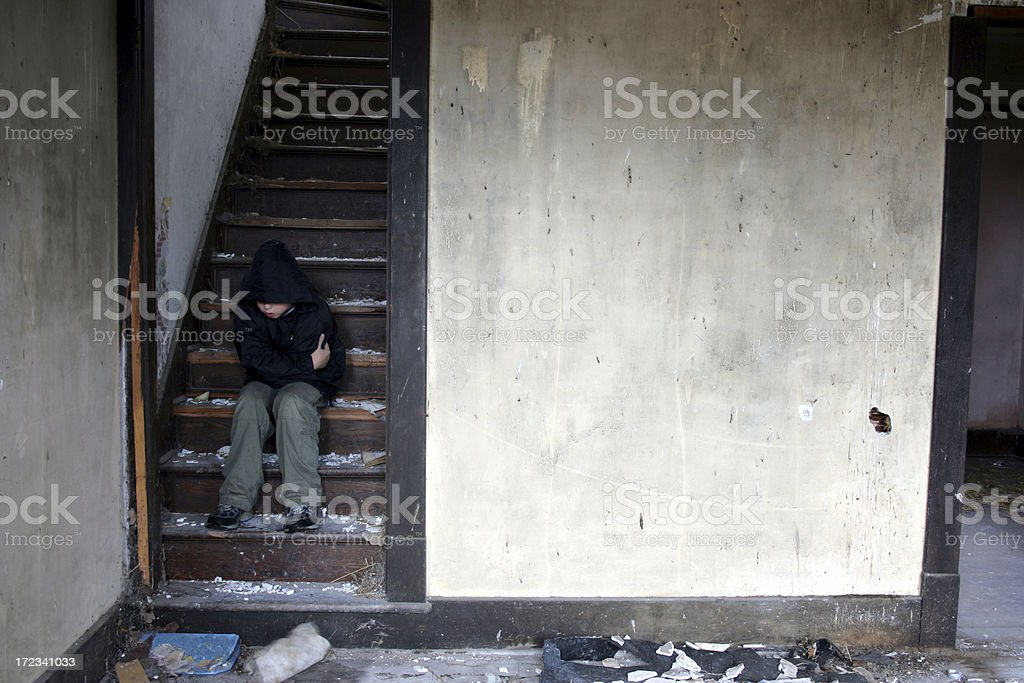 Cold child sitting on dirty stairs in water damaged home royalty-free stock photo