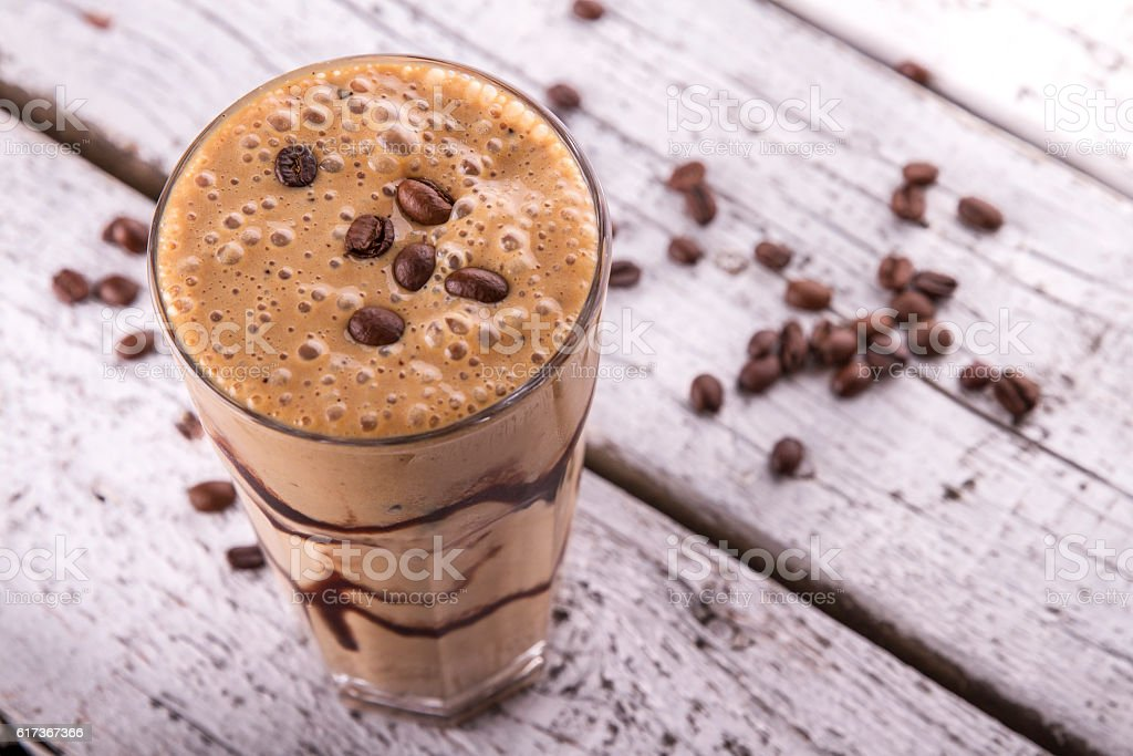 Cold chocolate milkshake frappe in tall glass with ice stock photo