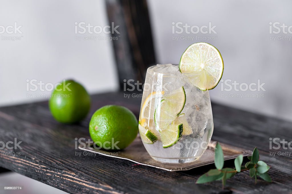 Cold cocktail with lime, lemon, tonic, vodka and ice stock photo