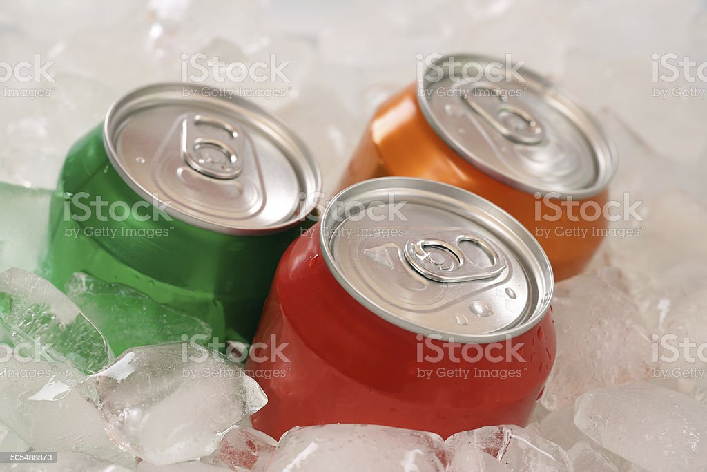 Cold cola and lemonade in cans on ice cubes stock photo