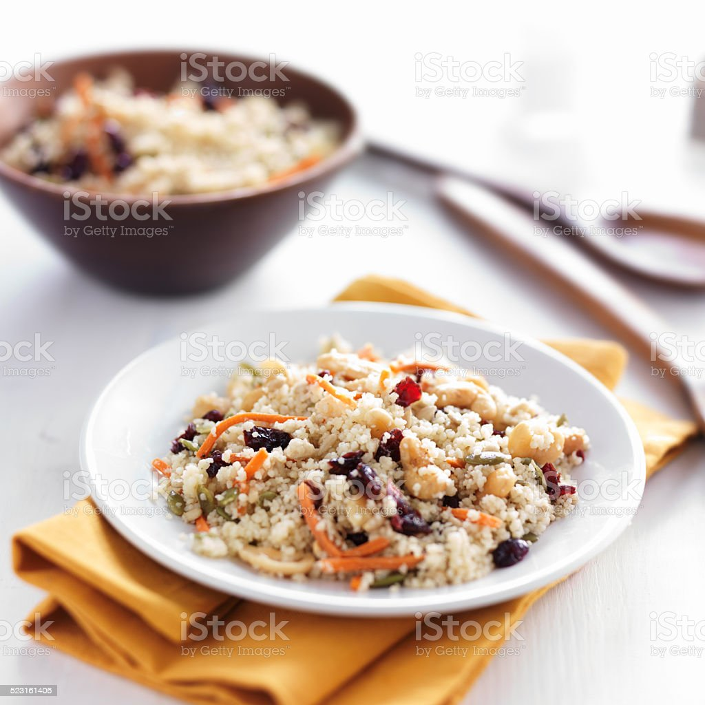 cold couscous salad with seeds and nuts on table top stock photo