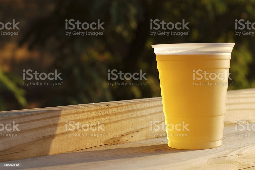 Cold Cup of Beer on a Deck Rail stock photo
