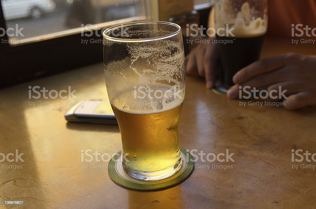 Cold draft beer in pint glass stock photo
