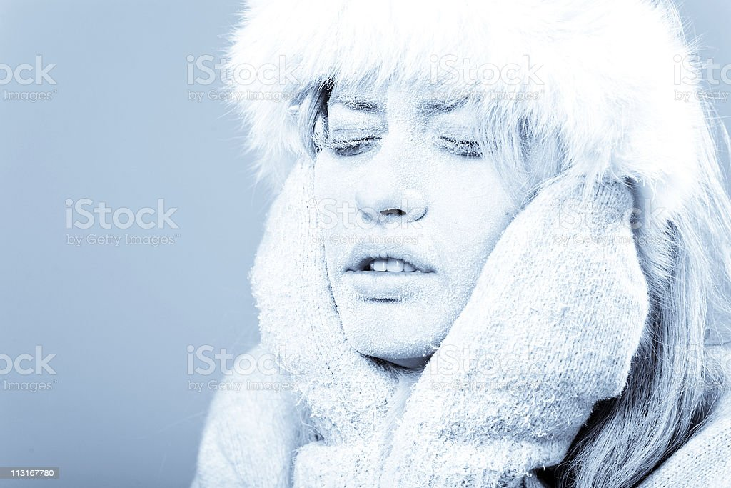 Cold female holding her face which is covered in ice royalty-free stock photo