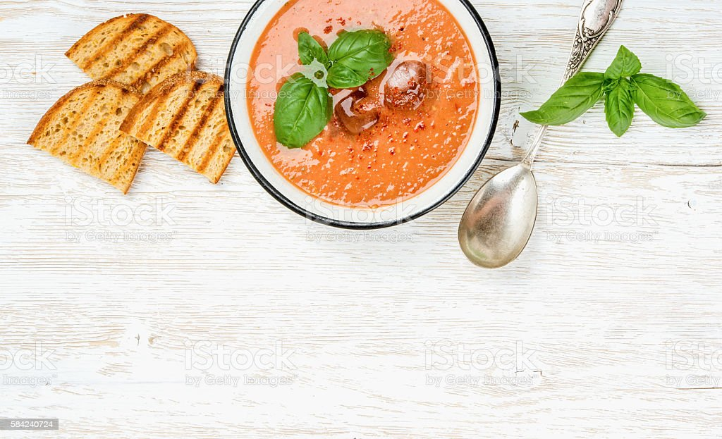 Cold gazpacho soup with ice, fresh basil and grilled bread stock photo
