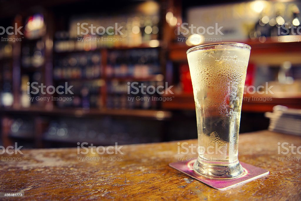 Cold Glass of Cider on Bar Counter in Irish Pub stock photo