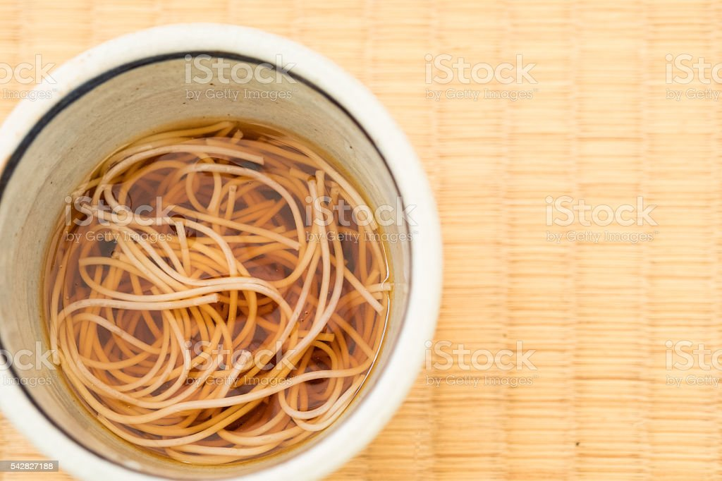 Cold, Japanese Soba Noodles in Dipping Sauce on Tatami Placemat stock photo