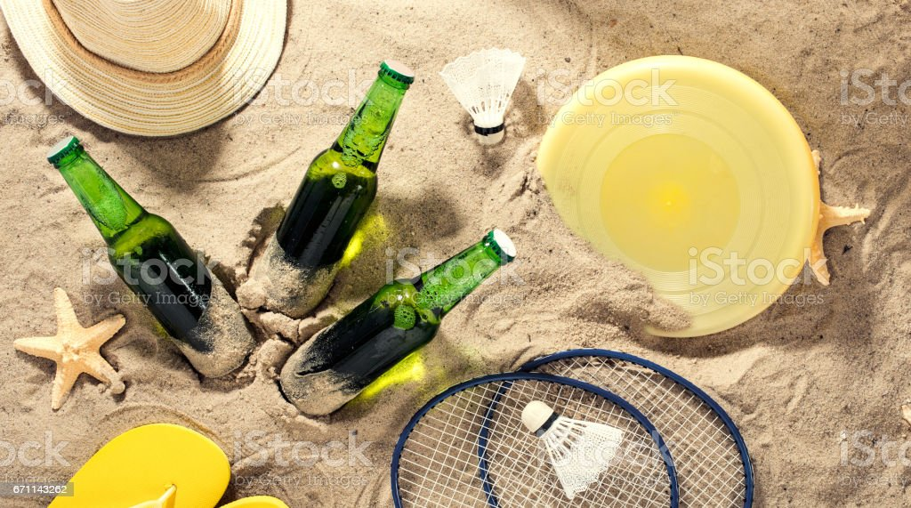Cold lager beer with items for beach activities on sand stock photo