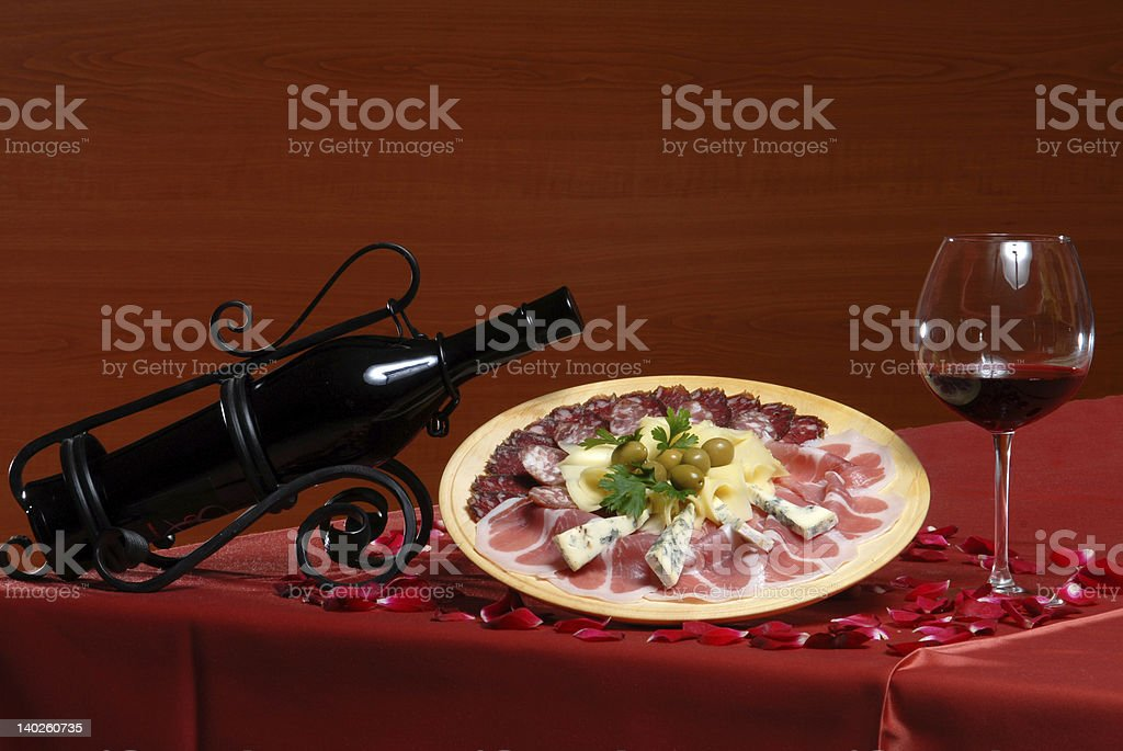 Cold meats with red wine and glass of vine royalty-free stock photo