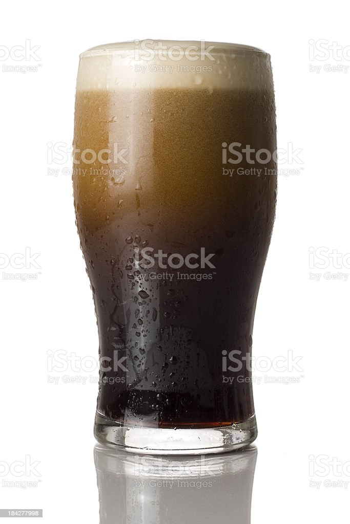 Cold pint of stout settling isolated on a white background royalty-free stock photo