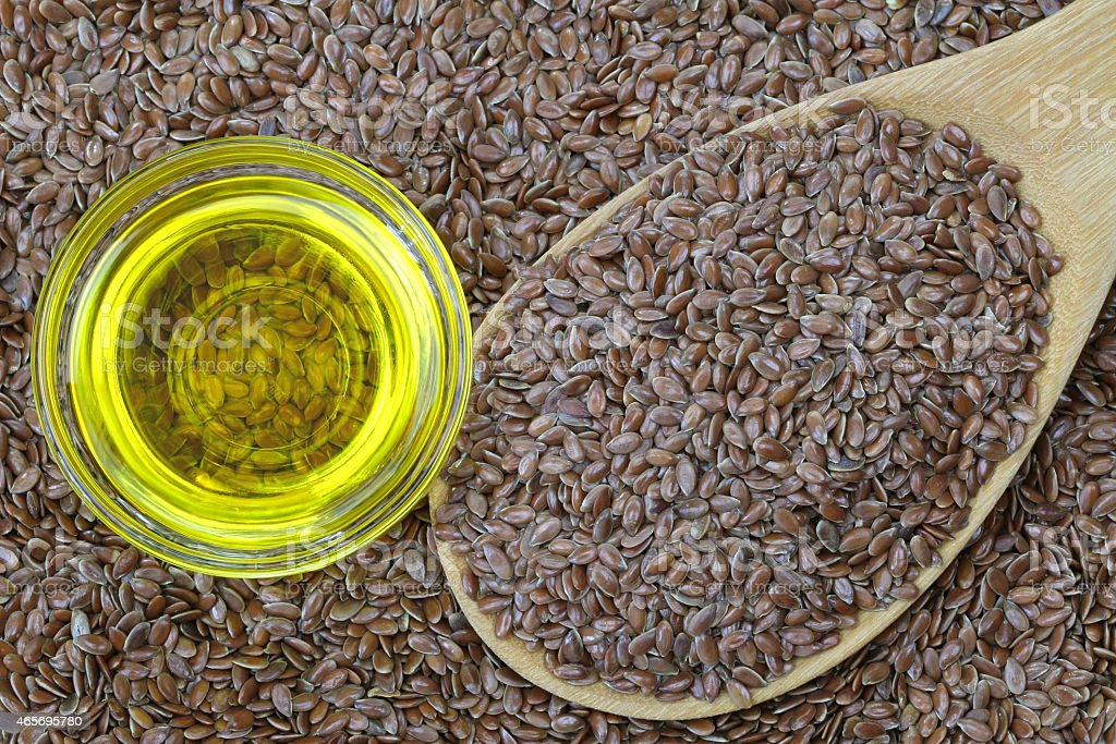 Cold pressed Linseed yellow oil on flax seeds stock photo