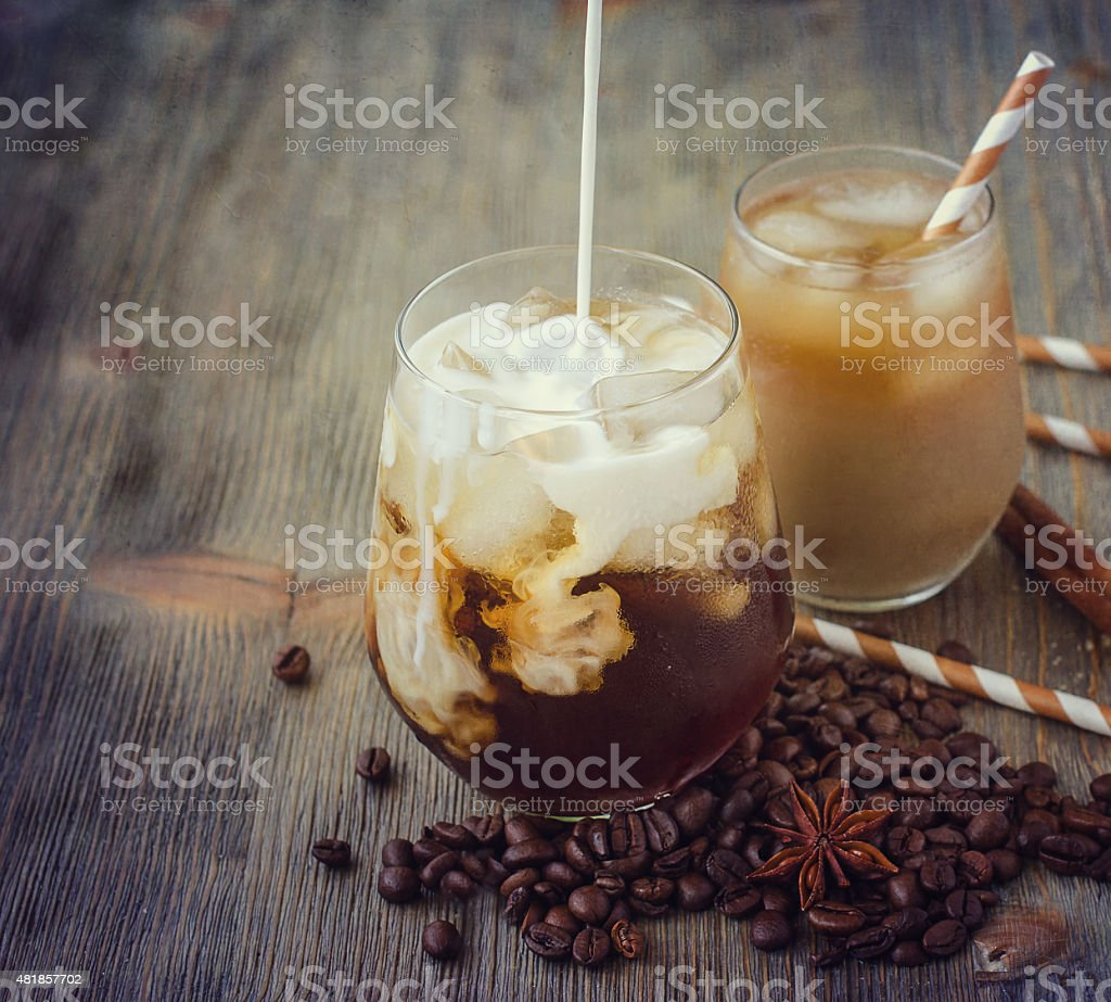 Cold refreshing iced coffee in glass with cubes of ice stock photo