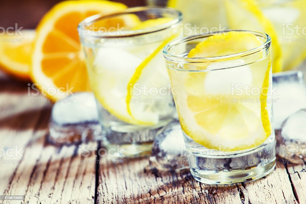 Cold Russian vodka with lemon and ice in shot glass stock photo