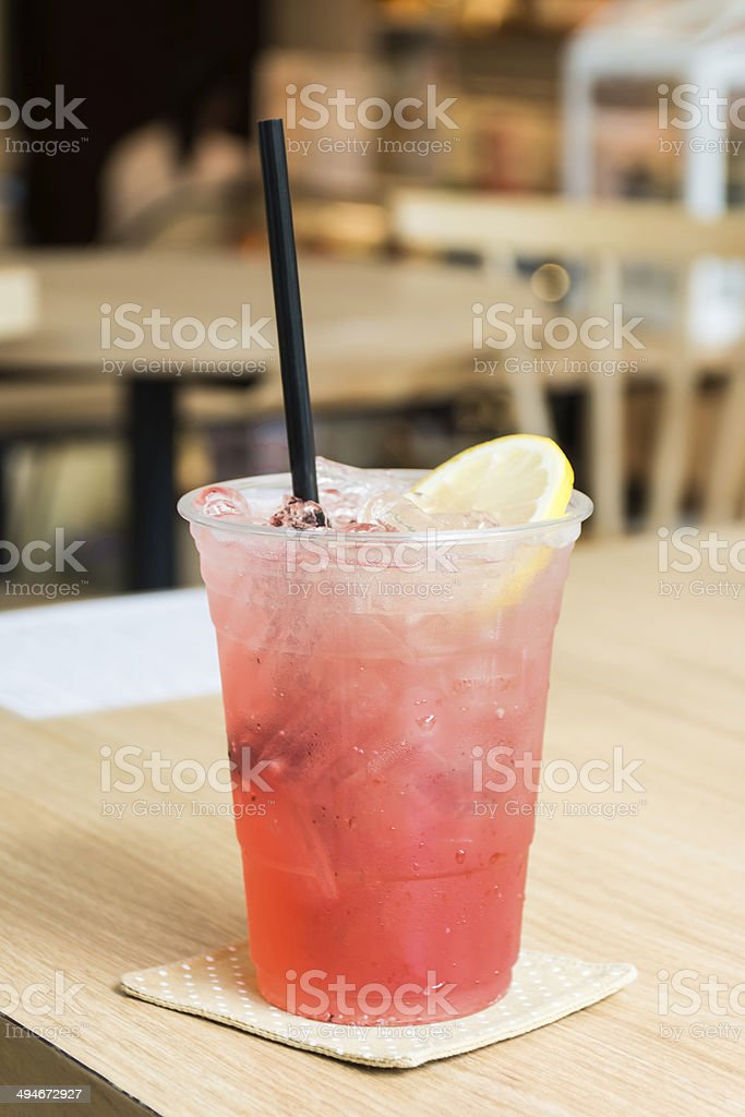 Cold Strawbery Italian soda in a glass with ice cubes stock photo